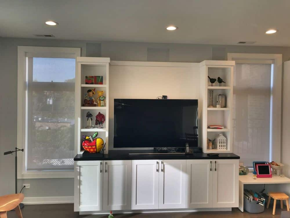A focused look at this TV stand featuring a large widescreen TV with built-in shelving on both sides, along with cabinetry below.