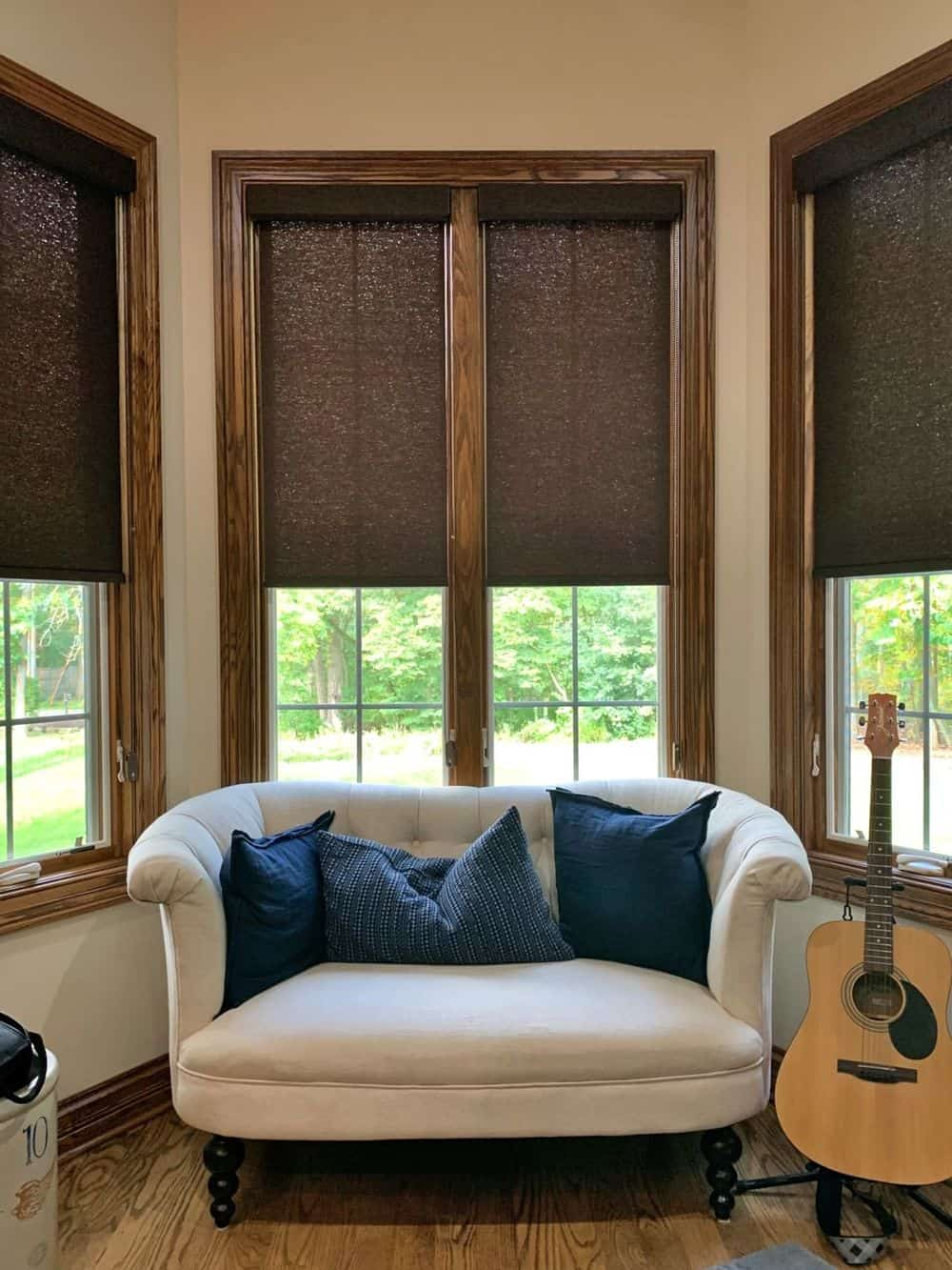 A focused look at this home's couch set by the windows featuring wooden frames and window shades.