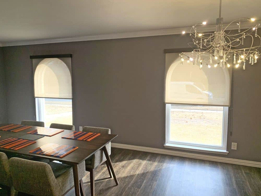 A dining area featuring a classy dining table and chairs set. The room features hardwood floors and gray walls and is lighted by a glamorous chandelier.