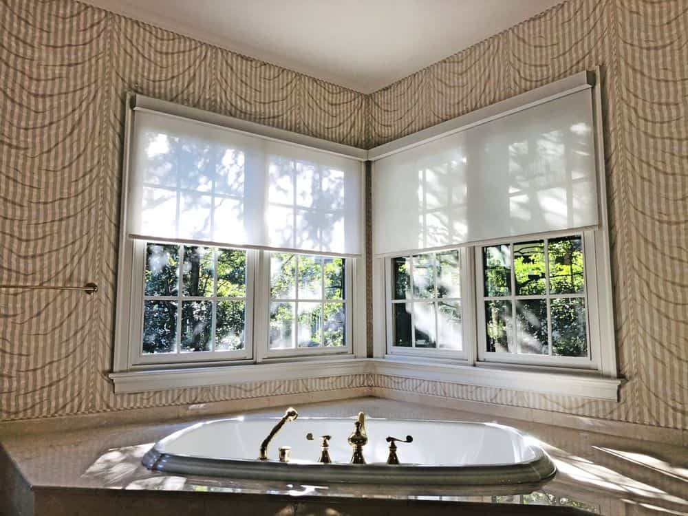 Master bathroom boasting decorated walls and a gorgeous drop-in corner tub. The windows feature window shades.