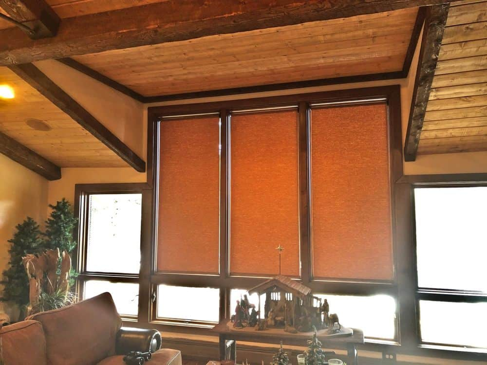 A focused look at this living space's stylish windows covered by window shades. The room features a rustic ceiling with beams, together with comfy seats.