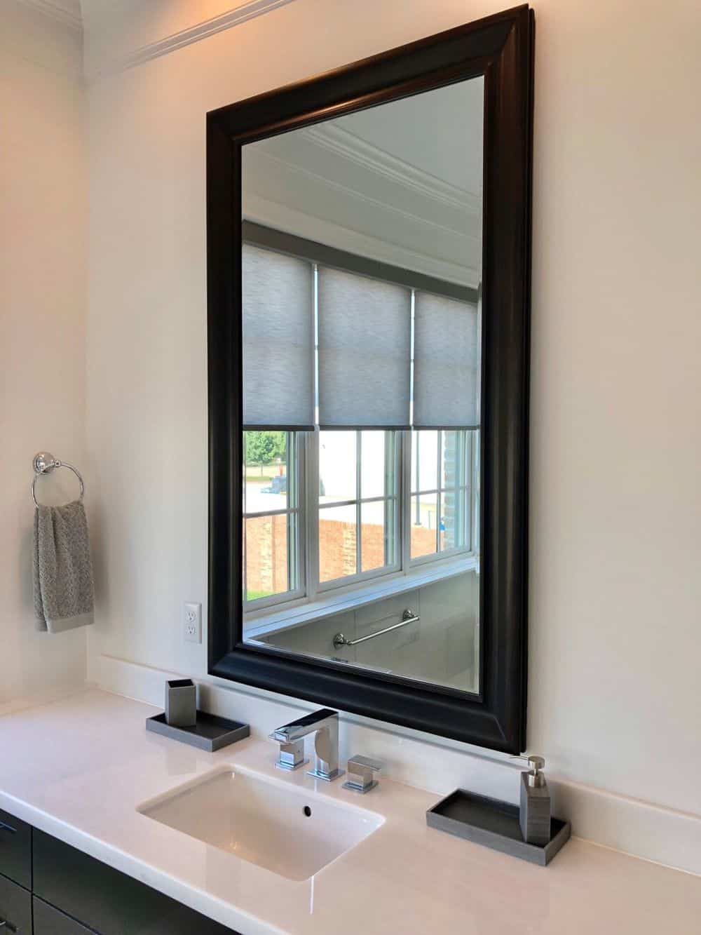 A focused look at this home's sink counter with a mirror reflecting the view of the windows behind, featuring window shades.