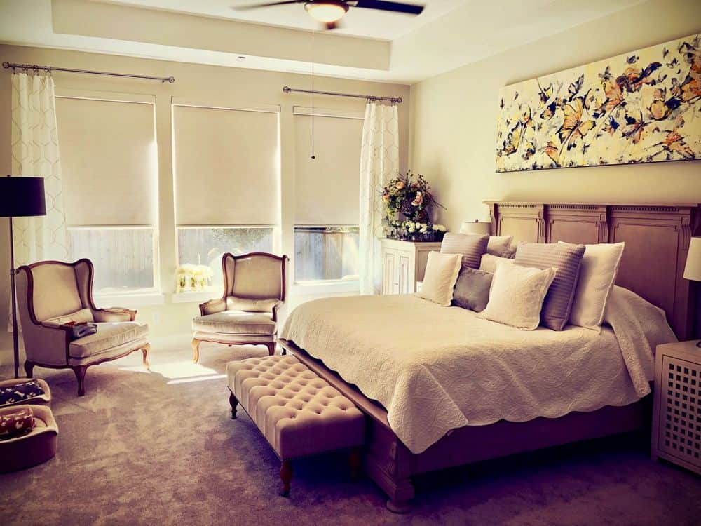 A master bedroom boasting a large elegant bed along with a sitting area on the side. The room features carpet flooring and a tray ceiling, along with glass windows with window shades.