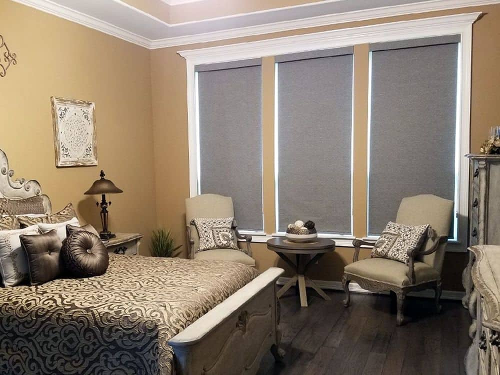 This primary bedroom boasts a luxurious bed set with a sitting area on the side. The room features hardwood floors, brown walls and a tray ceiling.