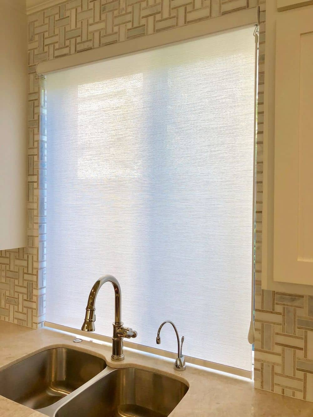 A focused shot at this home's kitchen window featuring a window shade. The stylish sink backsplash of the kitchen can be seen as well.