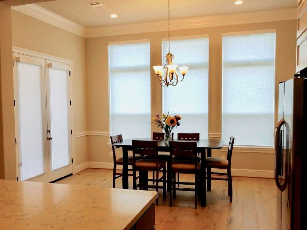 A dining area featuring a classy dining table set lighted by a gorgeous chandelier. The room has beige walls and hardwood floors.