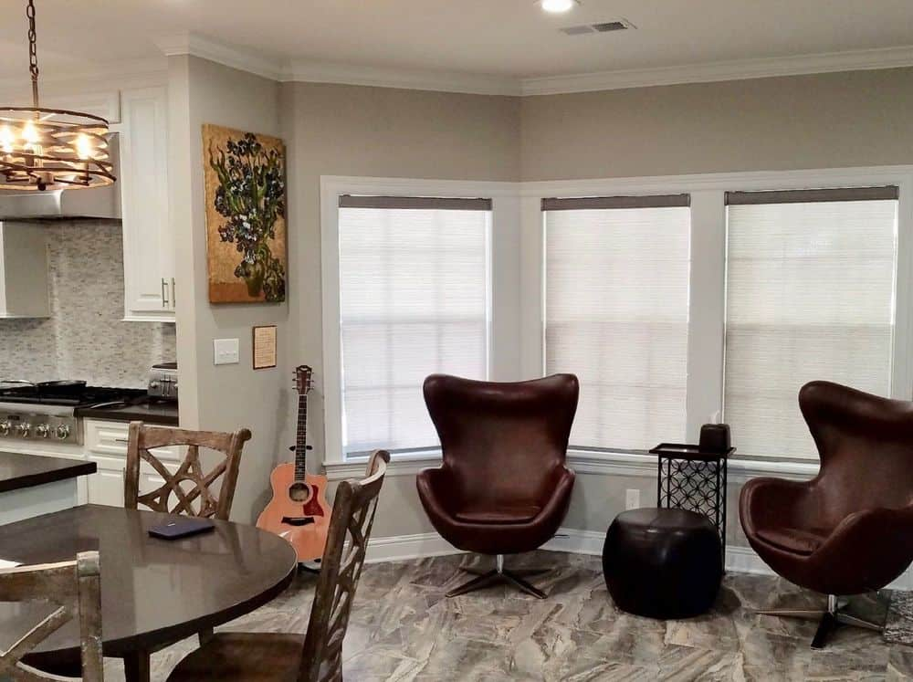 A dine-in kitchen featuring stylish tiles flooring. It has a nice breakfast bar area lighted by a modern ceiling light.