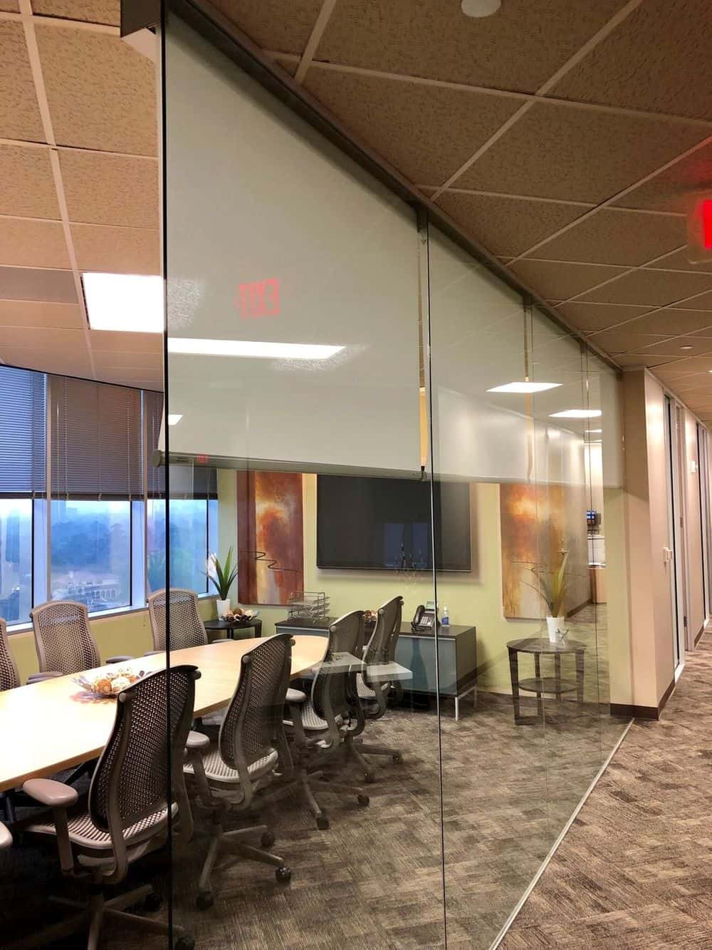 An office conference room featuring large glass walls, custom tiles ceiling and stylish carpet flooring. The room boasts a long rectangular table with modern office chairs, along with a large widescreen TV on the wall.