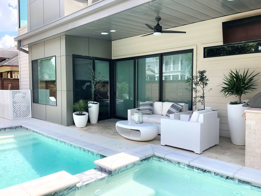 This home boasts a patio area and a very entertaining swimming pool area. The home's interior features roller window shades on its glass windows.