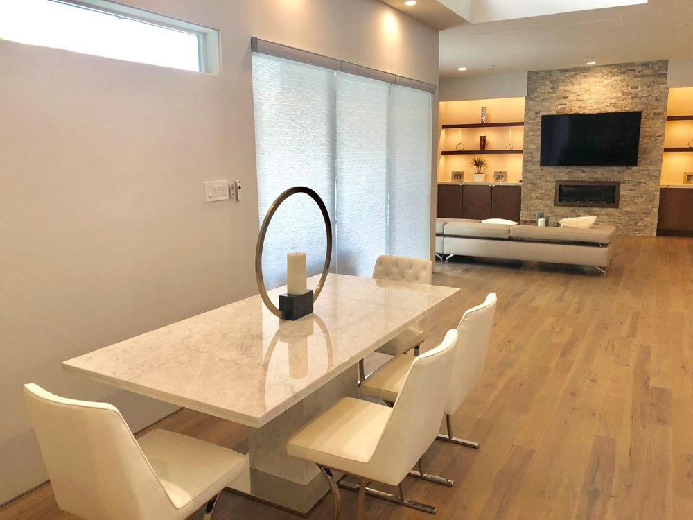 A dining area boasting a gorgeous dining table and chairs set. The house features hardwood floors and a custom ceiling.