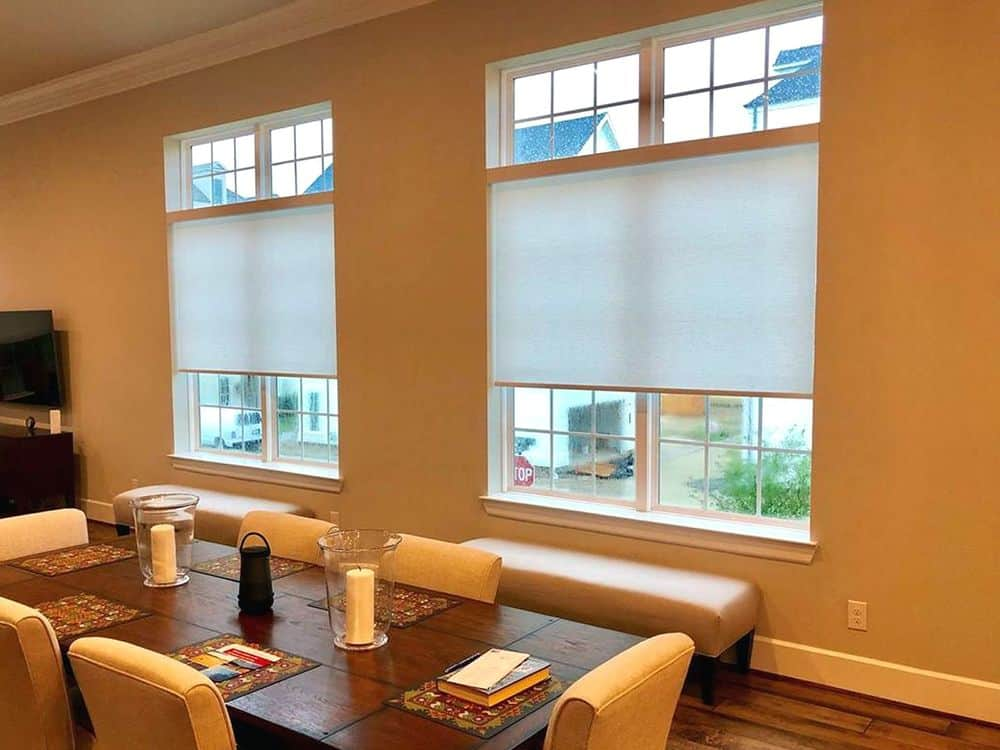 This dining room features rectangular wooden dining table with nice chairs. The area has hardwood floors and beige walls.