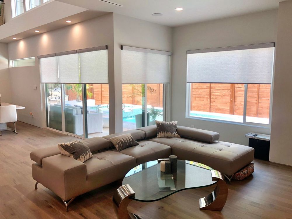 A spacious living space featuring a modern brown sofa set and a stylish heart-shaped center table. The home features hardwood floors and a custom ceiling with recessed ceiling lights.