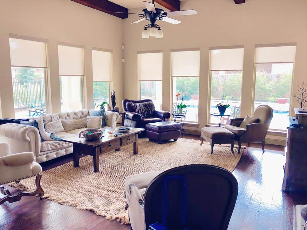 A large living space featuring white walls, hardwood floors and a ceiling with large beams. The room offers a set of comfy seats as well as a classy center table set on top of an area rug.