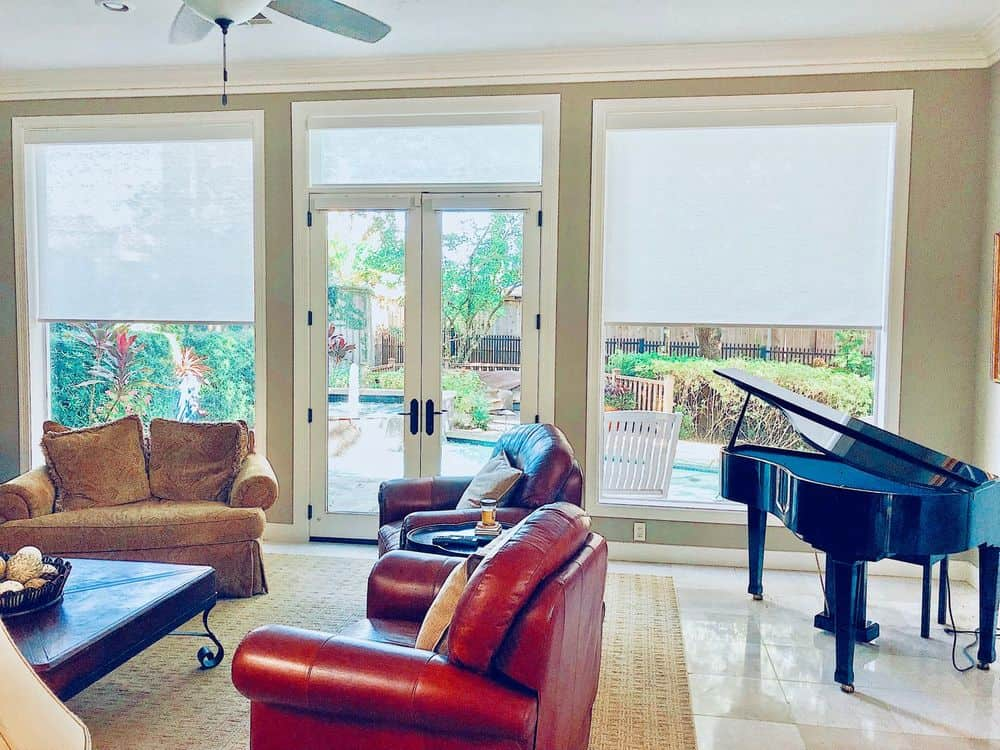 Large living space with an elegant set of furniture along with a black piano on the side. The room features tiles flooring topped by a large area rug along with large glass windows featuring window shades.