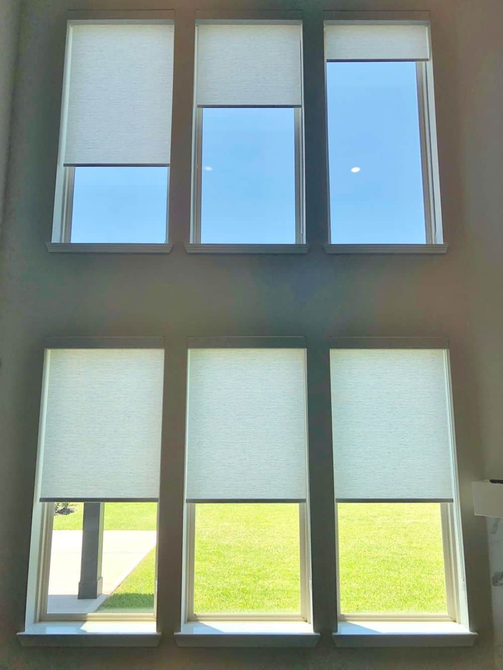 A focused shot at this home's windows featuring window shades. The house features gray walls and a high ceiling.