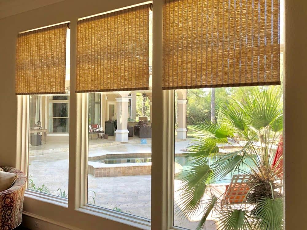 A focused look at this home's modern glass windows featuring wooden window shades. The lovely outdoor area can be seen through the windows.