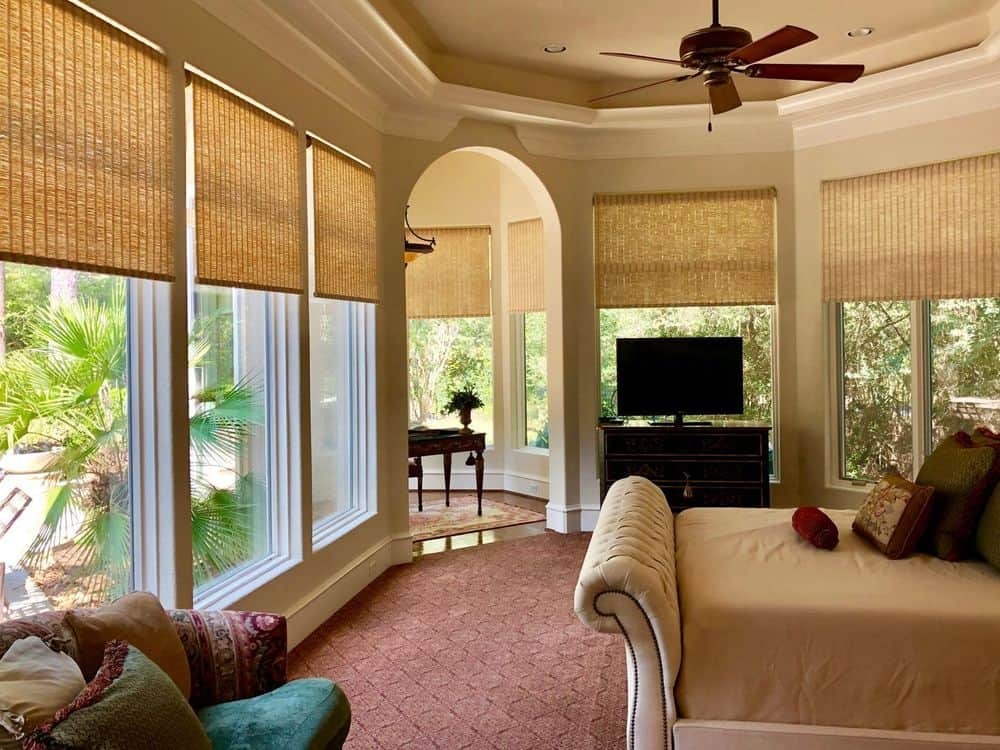 A custom primary bedroom boasting a luxurious bed and a private office area, along with a flat-screen TV on the side. The room features carpet flooring and a tray ceiling, along with glass windows featuring wooden window shades.