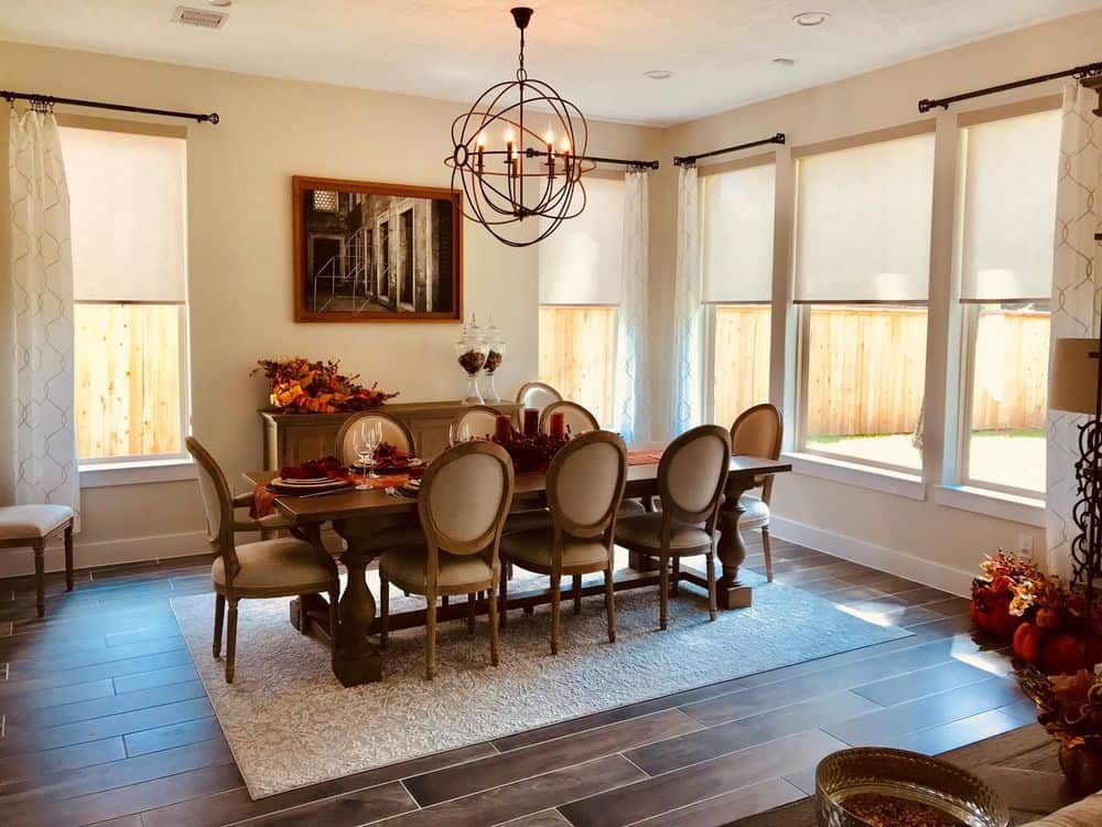 Dining area featuring an elegant dining table and chairs set on top of an area rug covering the hardwood flooring and is lighted by a charming chandelier.