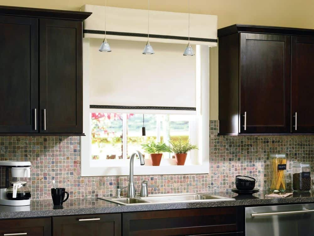 This kitchen features cabinetry and granite top kitchen counter, along with tiles backsplash and beige walls and ceiling.