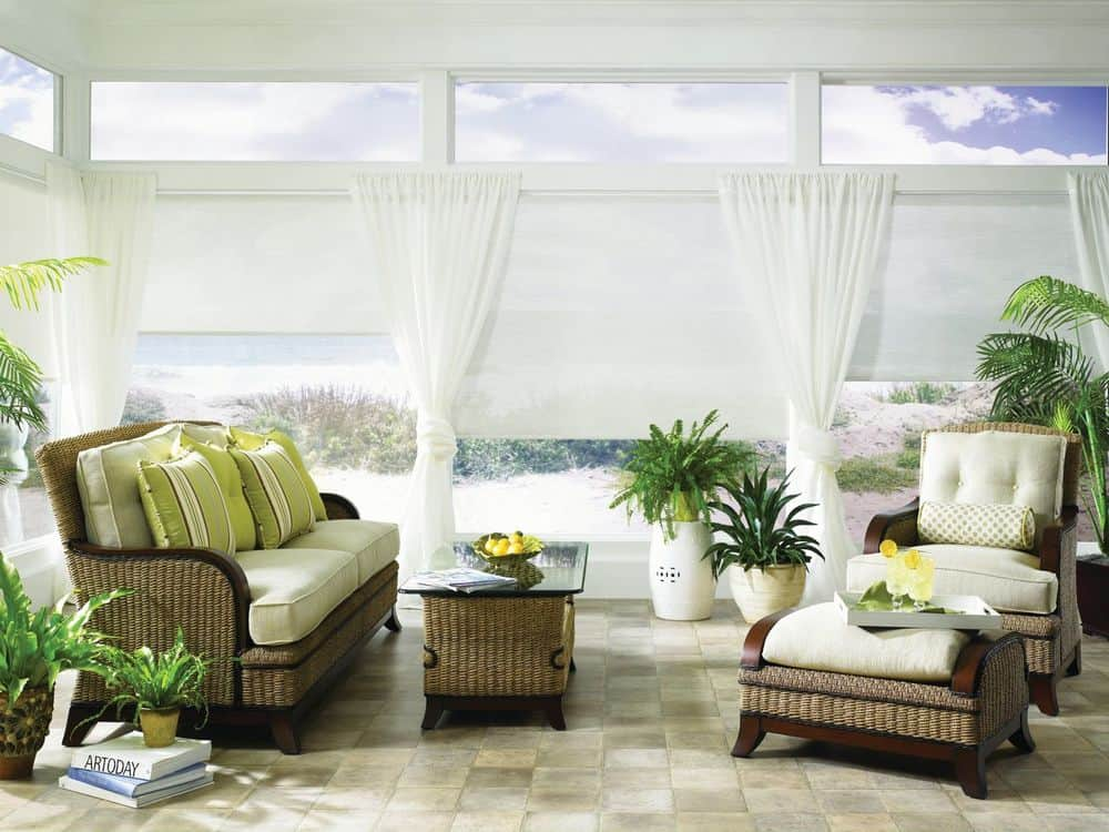 A lovely living space offering a nice set of seats, along with large glass windows featuring white window shades and white window curtains.