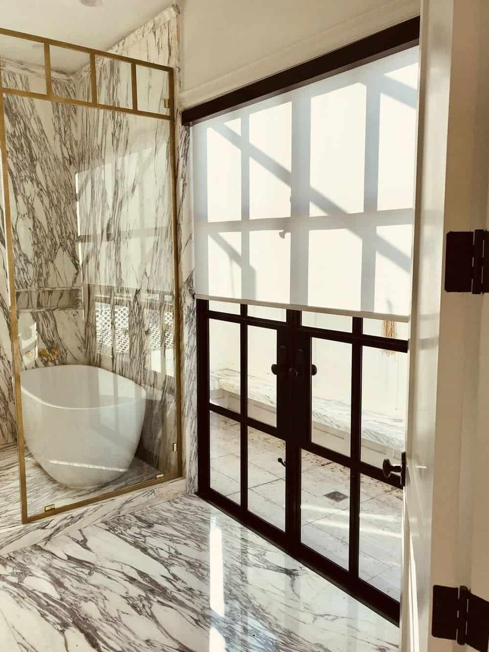 This primary bathroom boasts luxurious marble tiles floors and walls. It offers a freestanding tub as well. The windows of the room feature window shades.