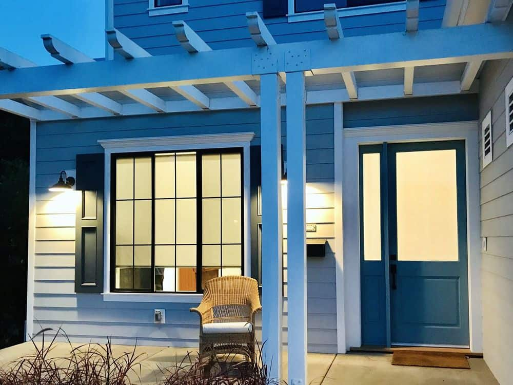 This house features a gray exterior and glass windows featuring window roller shades. It has a small patio area and a nice backyard as well.