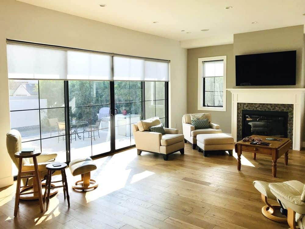 A spacious living space featuring hardwood floors and a regular ceiling lighted by recessed lights. The room has several sitting spots along with a fireplace and a flat-screen TV on the wall.