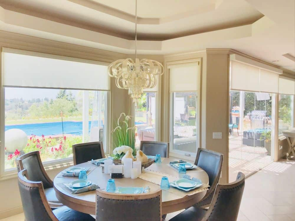 A dining area boasting an elegant round dining table set lighted by a luxurious chandelier hanging from the tray ceiling. The windows offer view of the outdoor area.