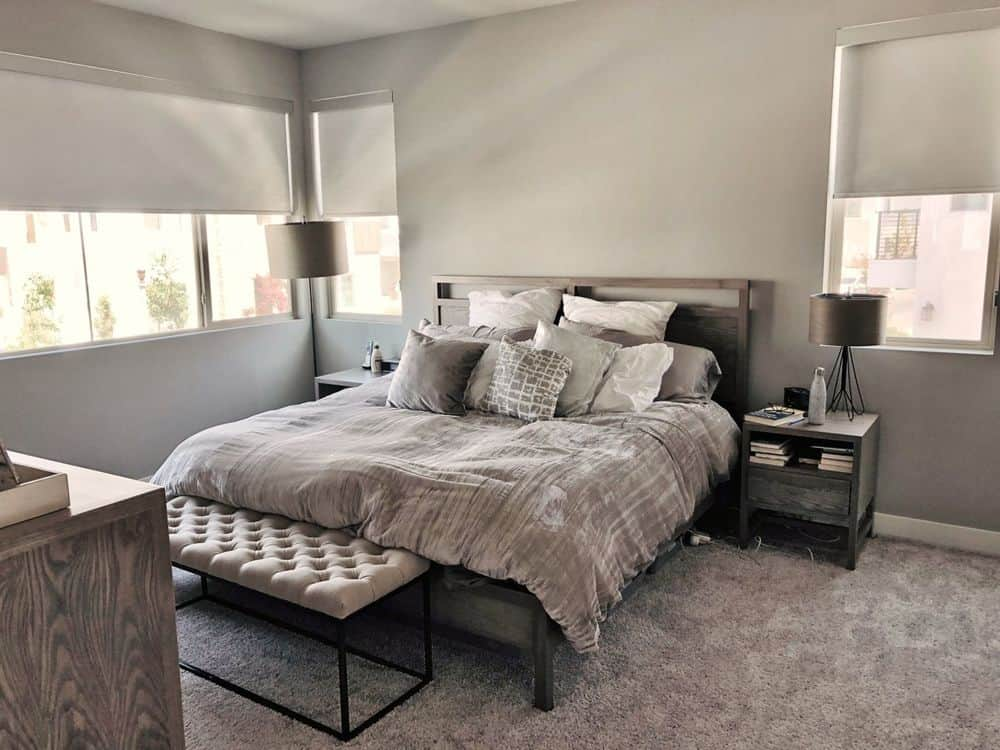 Primary bedroom featuring gray carpet flooring and gray walls. It offers a cozy bed set with two side table. The windows also feature roller window shades.