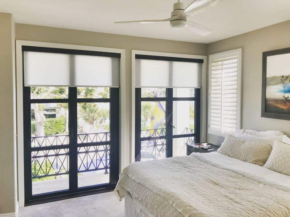 A master bedroom featuring a comfy bed set. The room has light gray walls and carpeted floors. There's a doorway leading to a private balcony area as well.