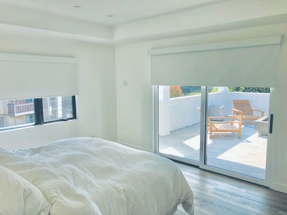 This guest room features white walls, hardwood floors and a white tray ceiling. It offers a lovely white bed set and windows and doors featuring roller shades.