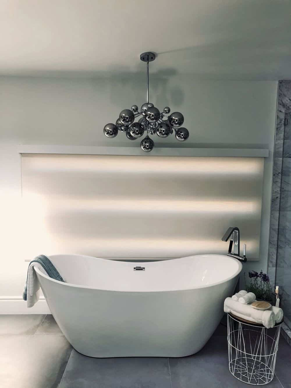 A focused look at this primary bathroom's freestanding tub set next to the window featuring a roller window shade and is lighted by a modern chandelier.