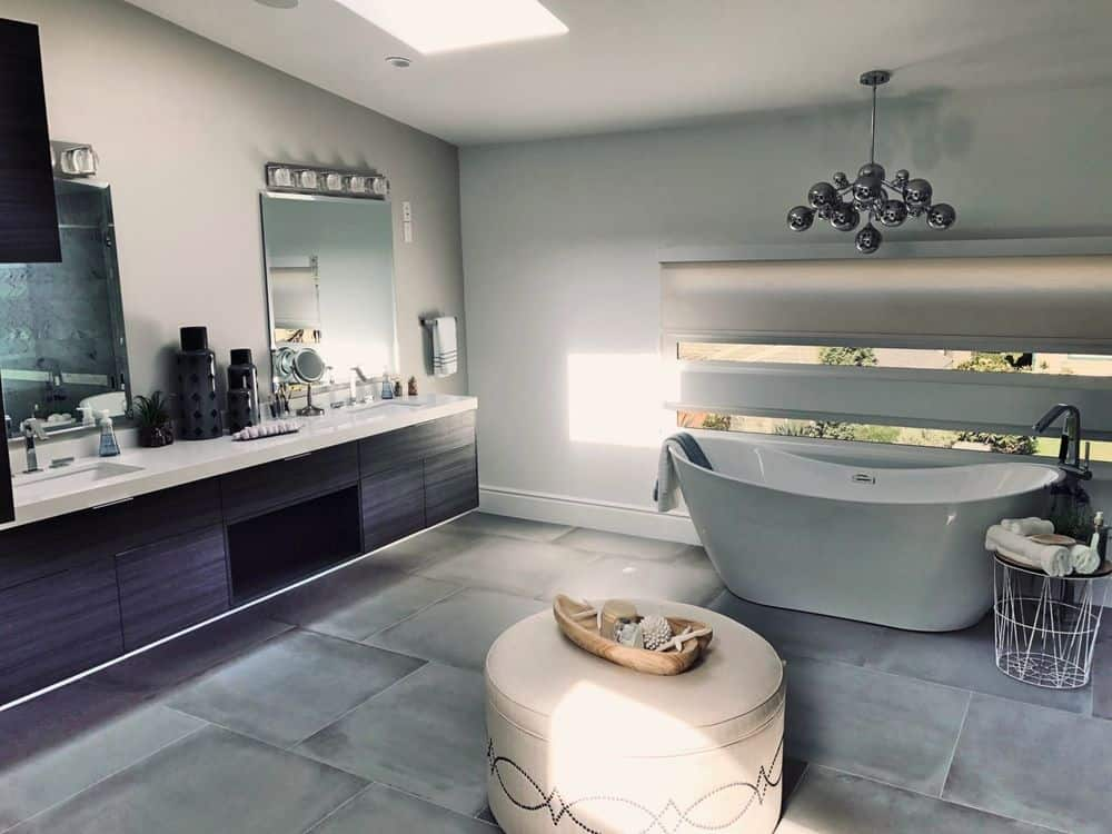 Large primary bathroom boasting a freestanding tub lighted by a modern chandelier, along with a floating vanity with two sinks and a powder desk. The room also features medium tiles flooring and a ceiling with a skylight.