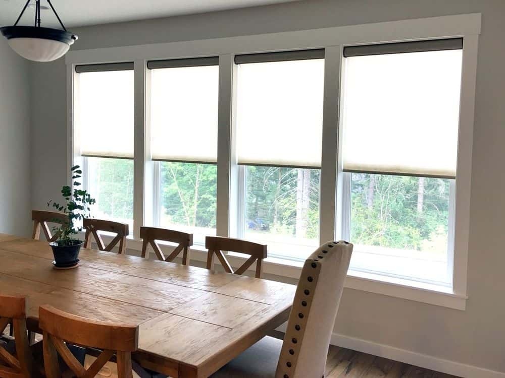 Dining area featuring a wooden rectangular dining table and chairs set surrounded by light gray walls and glass windows featuring roller window shades.
