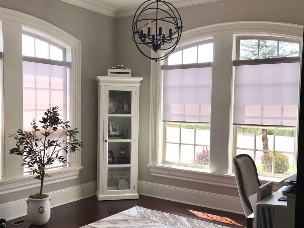 This home office features hardwood flooring topped by a stylish area rug, along with gray walls and a regular ceiling lighted by a modish ceiling light. The room offers an office desk and chair set along with a freestanding shelf in the corner.