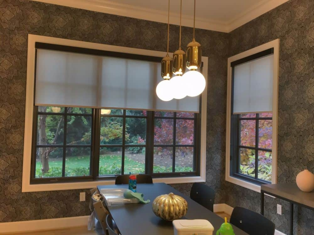 A dining room boasting a nice dining table and chairs set surrounded by elegantly decorated walls. The table set is lighted by charming ceiling lights. The windows feature roller window shades.