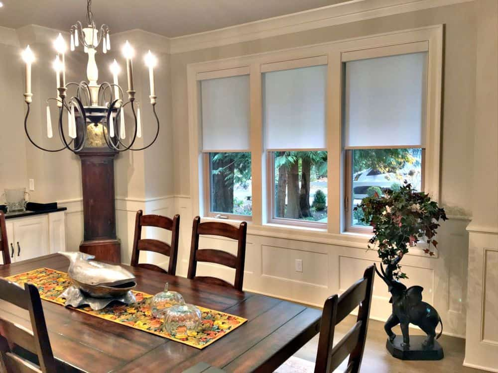 Dining room featuring a wooden dining table and chairs set lighted by a gorgeous chandelier. The room features glass windows with roller window shades.