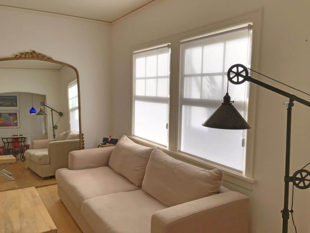 A living space featuring a comfy beige sofa set and a stylish floor lamp. The room features hardwood floors and windows featuring roller window shades.