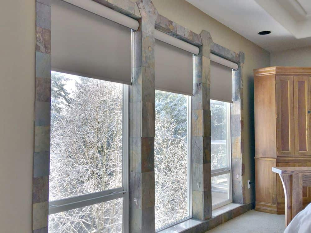 A closer look at this home's stylish glass windows frame with a roller window shade. The area has carpet flooring and a tray ceiling.