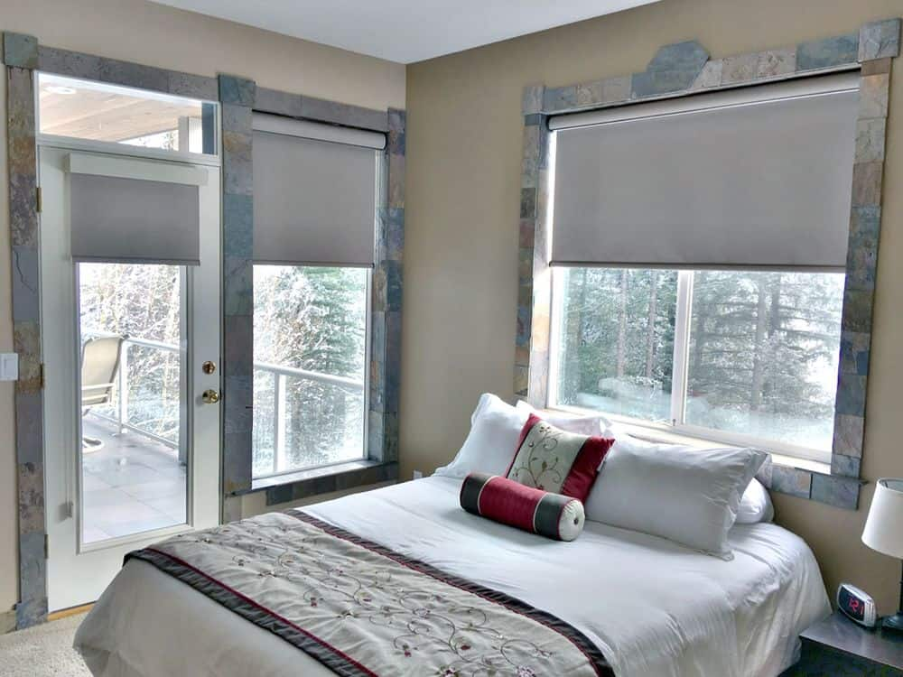 A guest room featuring stylish windows and door frame along with glass windows with roller window shades. The room offers a comfy bed set and a doorway leading to a private balcony.