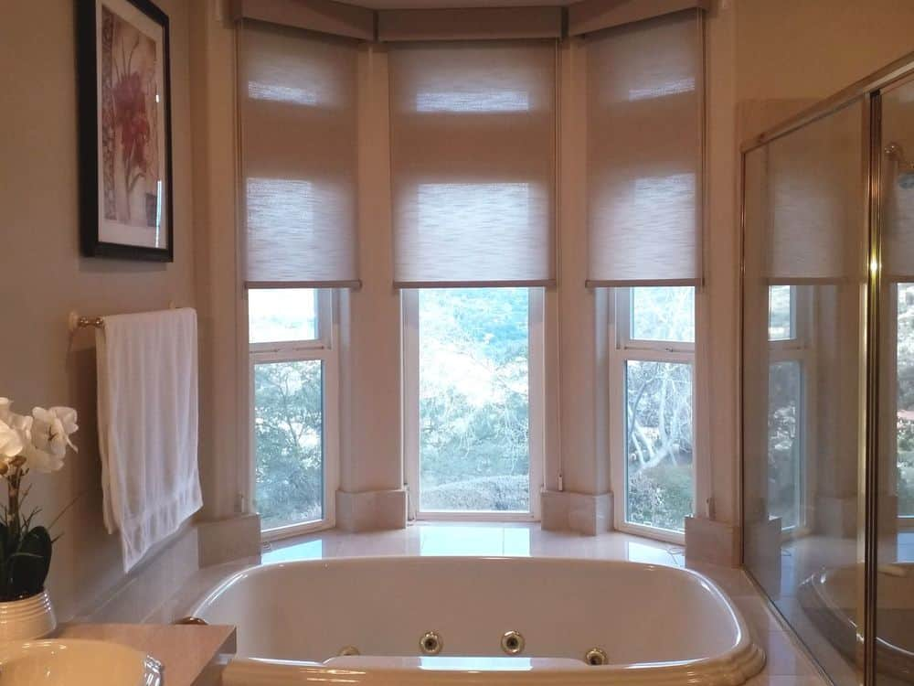 A primary bathroom with a walk-in shower and a drop-in deep soaking tub by the windows with roller window shades.