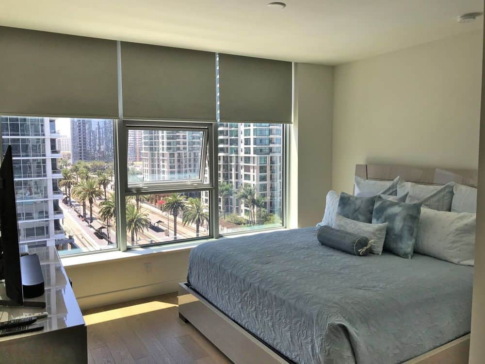This bedroom offers a comfortable modern bed along with a widescreen TV set in front. The glass windows also feature window shades.