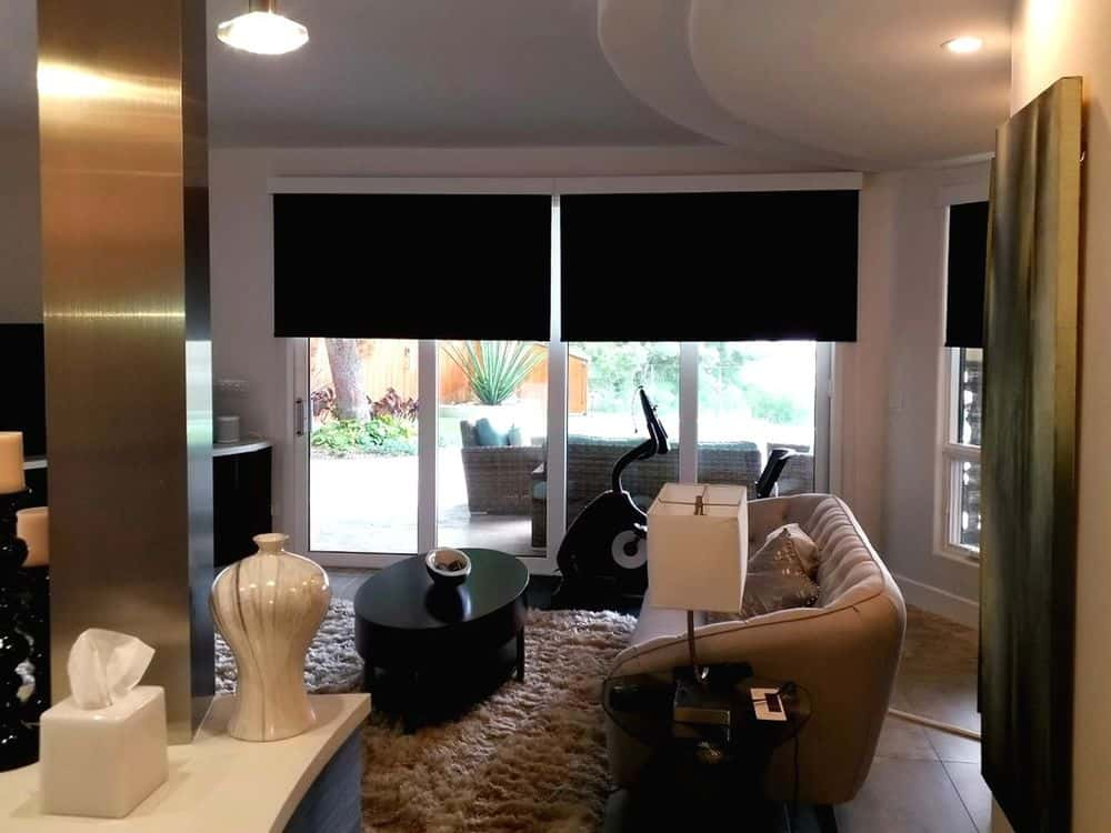 A living space featuring an elegant sofa set along with a stylish espresso-finished center table on top of the area rug covering the hardwood flooring. The area features a custom ceiling and windows with black roller window shades.