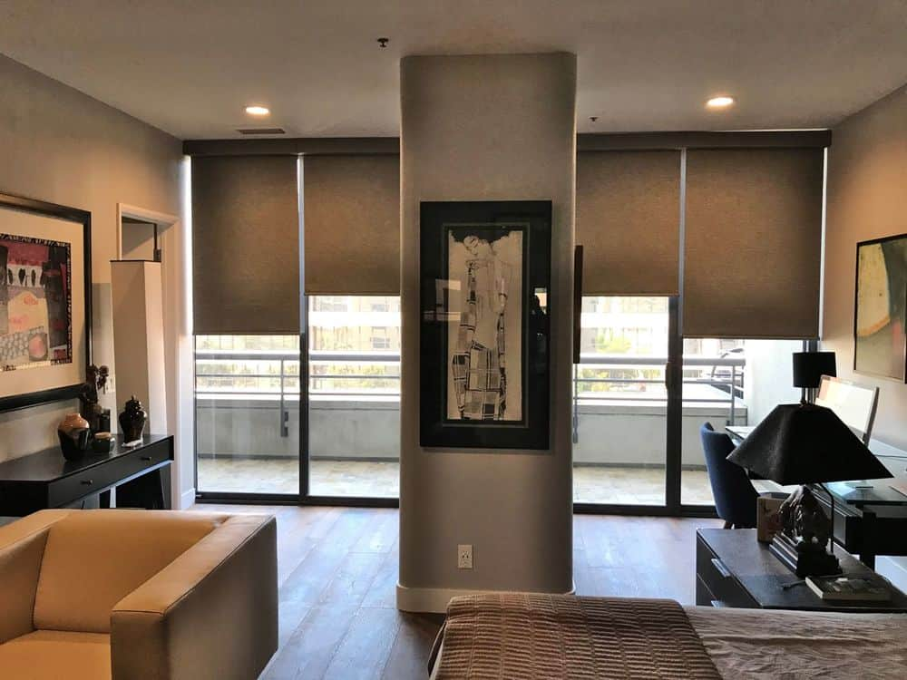 A primary suite featuring a cozy bed set, a sitting area on the side and a study desk and chair on the side lighted by table lamps. The room features hardwood floors and a regular ceiling with recessed ceiling lights.