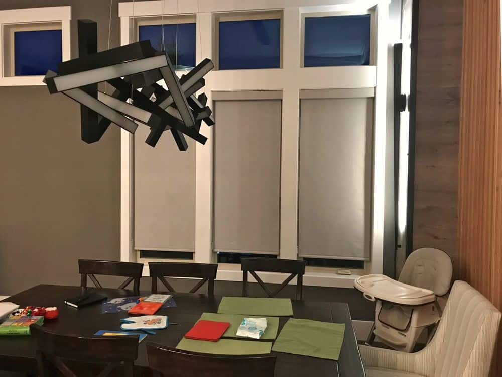 This dining area features a nice dining table and chairs set lighted by a stunning ceiling light hanging from the tall ceiling. The area's windows are covered by roller window shades.