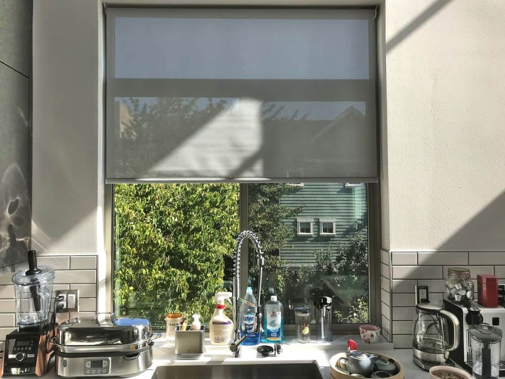 A focused look at this kitchen's glass window with a gray roller window shade. This kitchen also features tiles backsplash and a white kitchen countertop.