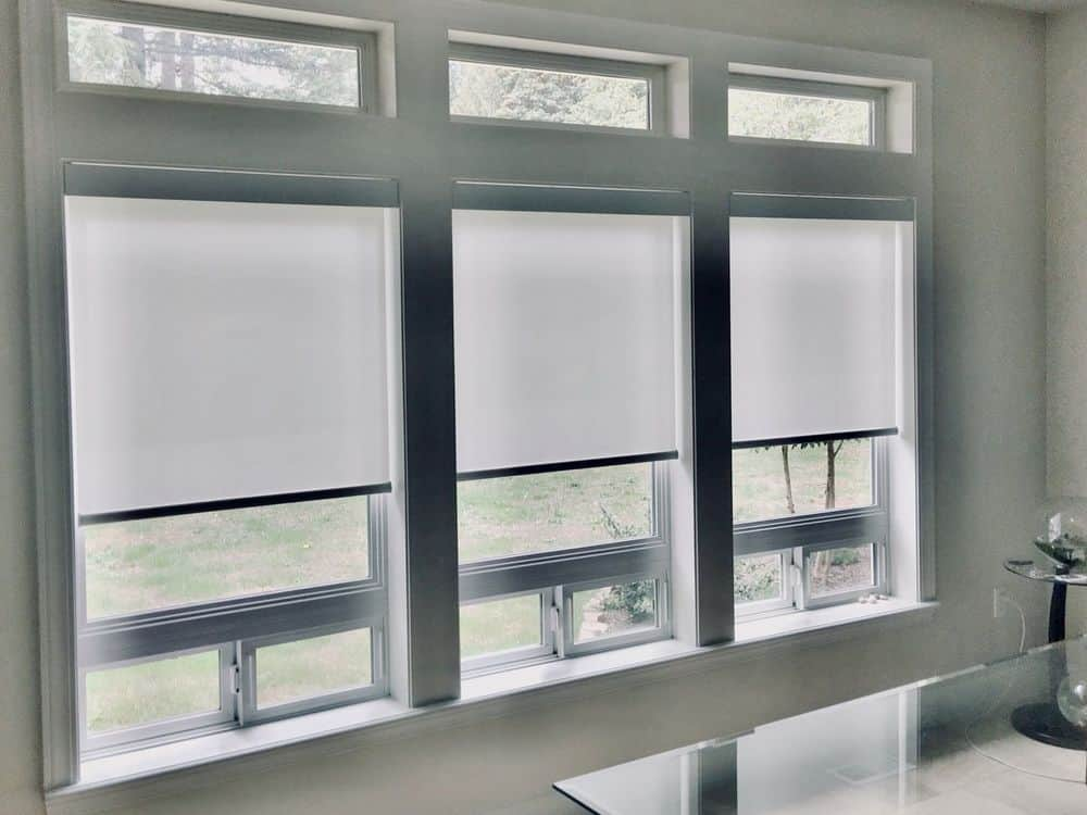 A closer look at this modern home's glass windows featuring roller window shades, set in the home's dining area.