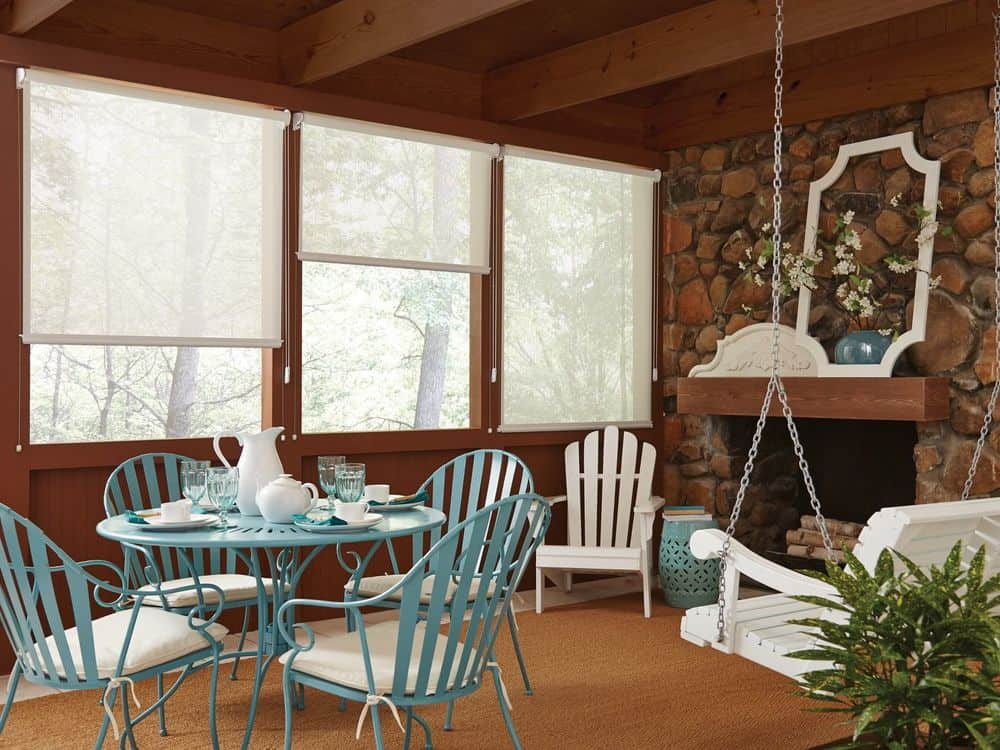 A dining nook area featuring a lovely table set and a swinging seat on the side. There's also a fireplace. The room features a rustic ceiling and brown carpet flooring together with roller window shades.