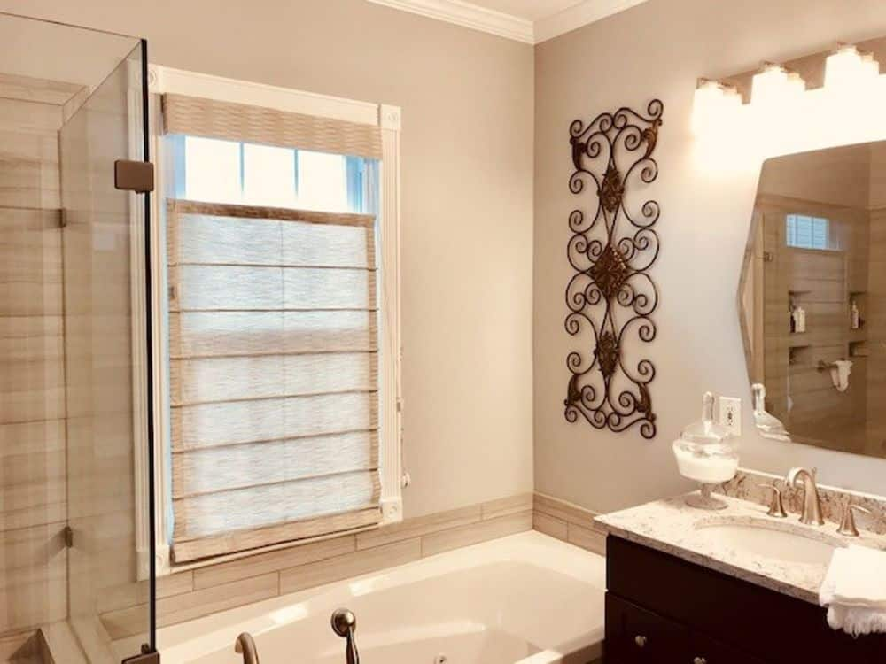 A primary bathroom featuring a walk-in shower and a drop-in soaking tub, along with a marble top sink counter lighted by classy wall lights.