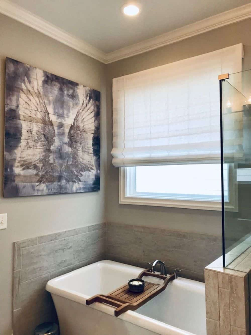 A master bathroom featuring a walk-in shower and a freestanding tub set near the window with a Roman-style window shade. The wall decor looks very attractive.